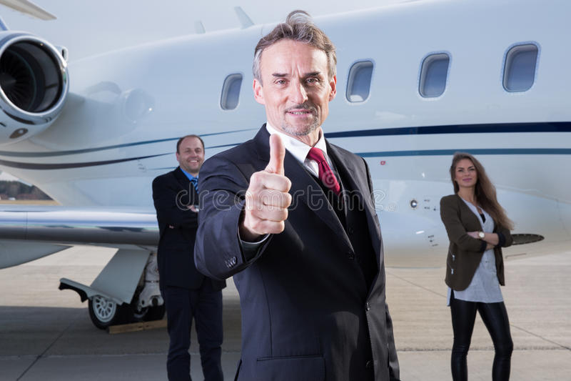 Thumbs up business team in front of corporate private jet. Man showing gesture royalty free stock image