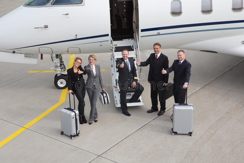 Thumbs up in front of plane - executive business team stock photo