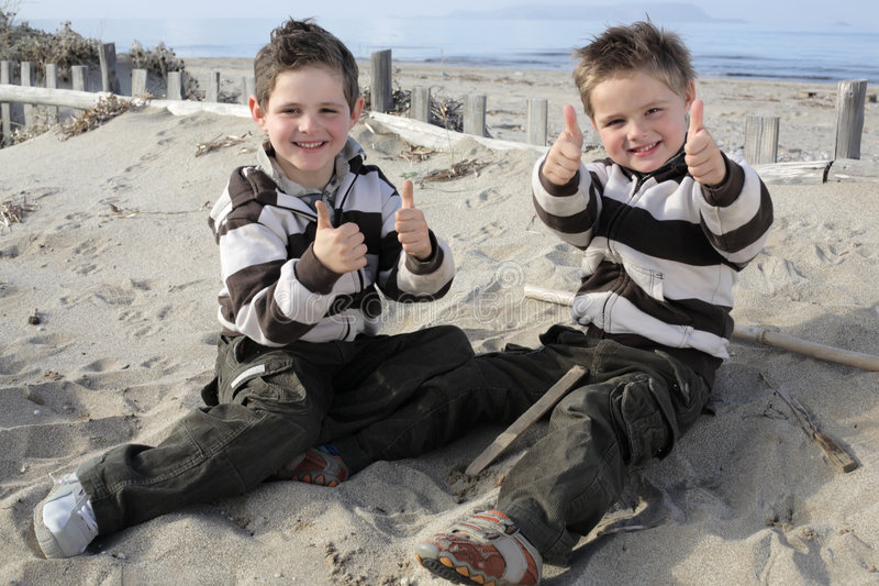 Thumbs up for the fun, boys!. Two little boys sitting on the beach showing thumbs up royalty free stock photo