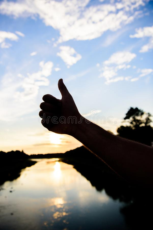 Thumbs up gesture sign of best choice approve and accept. Silhouette thumb up gesture in front of sunset above river stock image