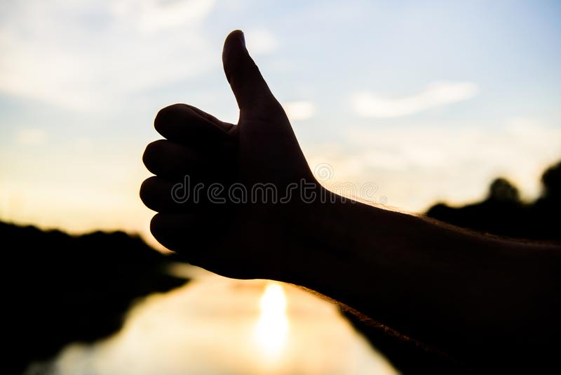 Thumbs up gesture sign of best choice approve and accept. Top places to visit in evening. Silhouette thumb up gesture in stock photo