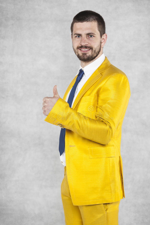 Thumbs up for a gold suit. Man wearing gold suit stock images