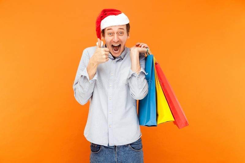Thumbs up, like sign. Man shopaholic in red cap, holding many co stock photography