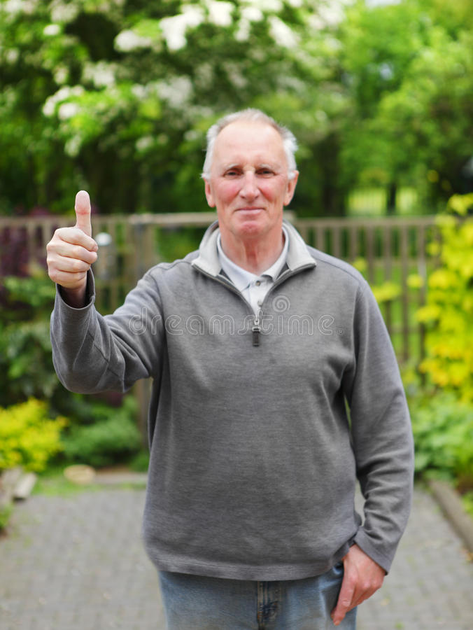 Thumbs up old man in garden stock images