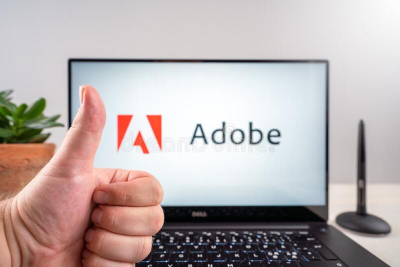 Thumbs up over Adobe logo and wacom stylus pen. To illustrate the fair treatment of artists on the adobe microstock platform. Compared to microstock agency royalty free stock photo