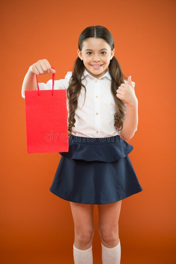 Thumbs up for sale. Cute small child showing ok sign to purchase bought at sale on orange background. Happy little girl. Holding shopping bag after seasonal royalty free stock photos