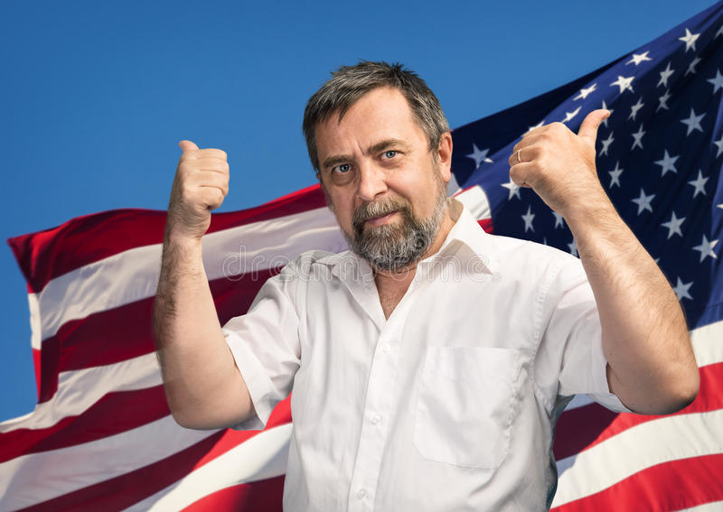 Thumbs up sign against USA flag. Patriotic concept. Man with thumbs up sign against United States of America flag stock photography