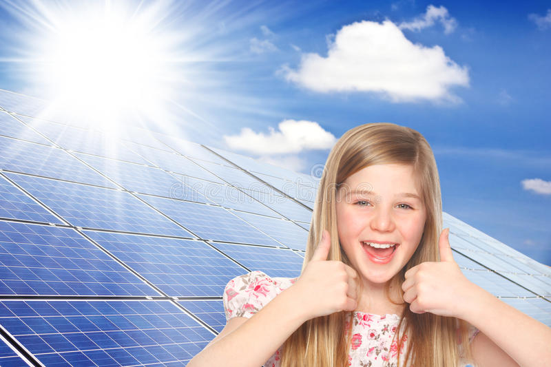 Thumbs up for solar power. Cute girl shows thumbs up for photovoltaic cells royalty free stock image