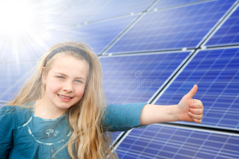 Thumbs up for solar power. Cute girl gives thumbs up for photovoltaic cells royalty free stock photos