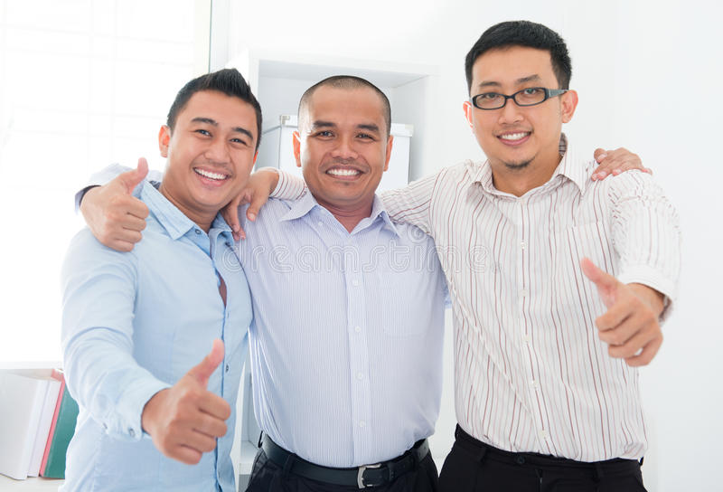 Thumbs up Southeast Asian businessmen. Standing in office royalty free stock photo