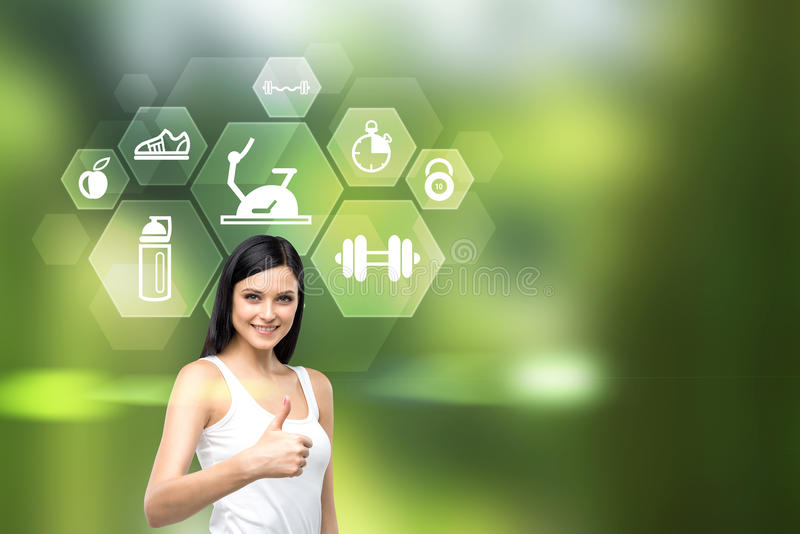 Thumbs up sporting goods. Pretty caucasian female showing thumbs up and icons with sporting goods on green background stock photo