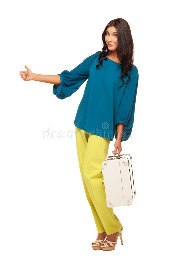 Thumbs up to catch your taxi. Woman with suitcase is trying to catch a taxi on isolated white background stock photography