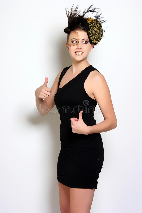 Thumbs Up. Woman dressed in a little black cocktail dress with a cute hat and feathers in her hair stock image