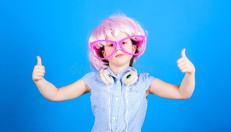 Thumbs ups for comfortable headphones. Little girl in fancy glasses wearing headphones and pink hair wig. Small child. With modern wireless headphones. Cute kid royalty free stock photo