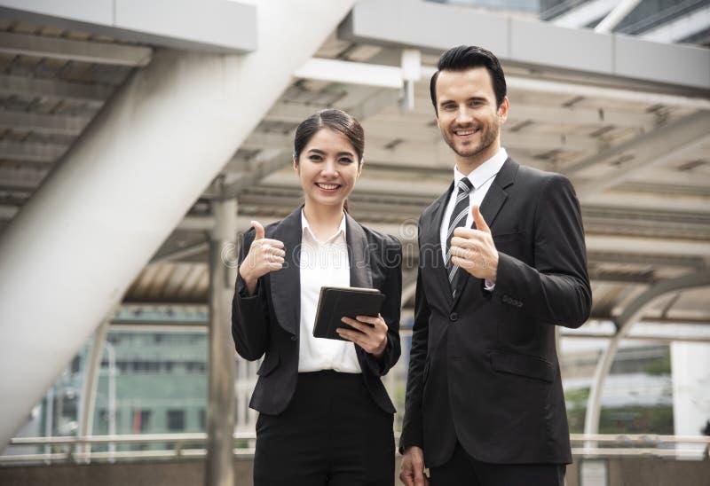 Thumbsup della mano di gesto del partner della donna di affari e dell'uomo d'affari immagini stock