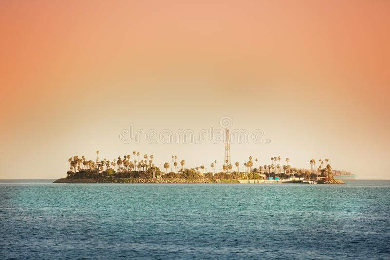 THUMS artificial Island Chaffee at the sunset. The THUMS artificial Island Chaffee built for offshore oil extraction, disguised with palm trees, California royalty free stock photo