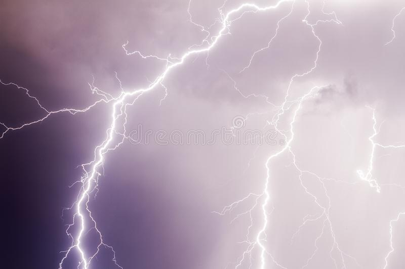 Thunder storm lightning strike on the dark purple cloudy sky royalty free stock photos