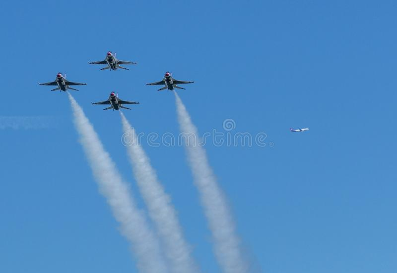 Thunderbirds del U.S.A.F. en la formaci?n de diamante con el avi?n comertial en distancia fotos de archivo