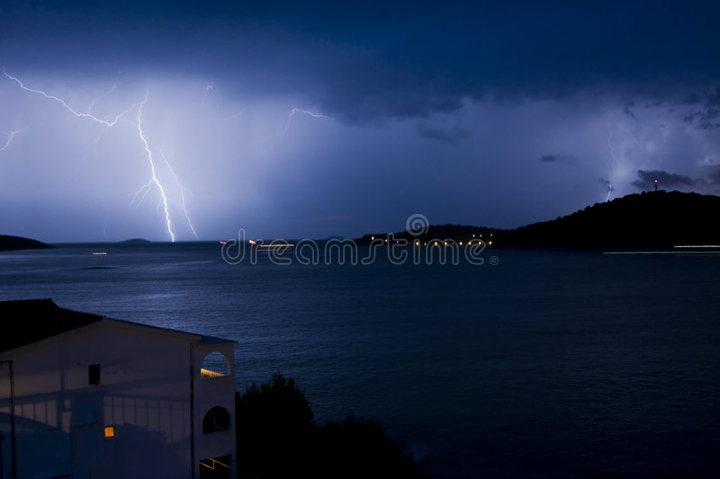 Thunderstorm. Multiple Thunders during storm with house and city lights - Razanj - Croazia 2007 royalty free stock image