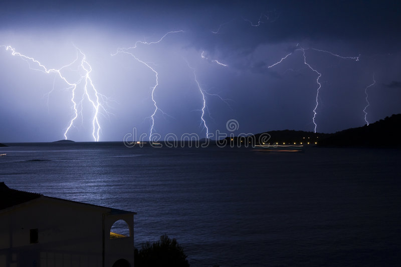 Thunderstorm. Multiple Thunders during storm with house and city lights - Razanj - Croazia 2007 stock photo