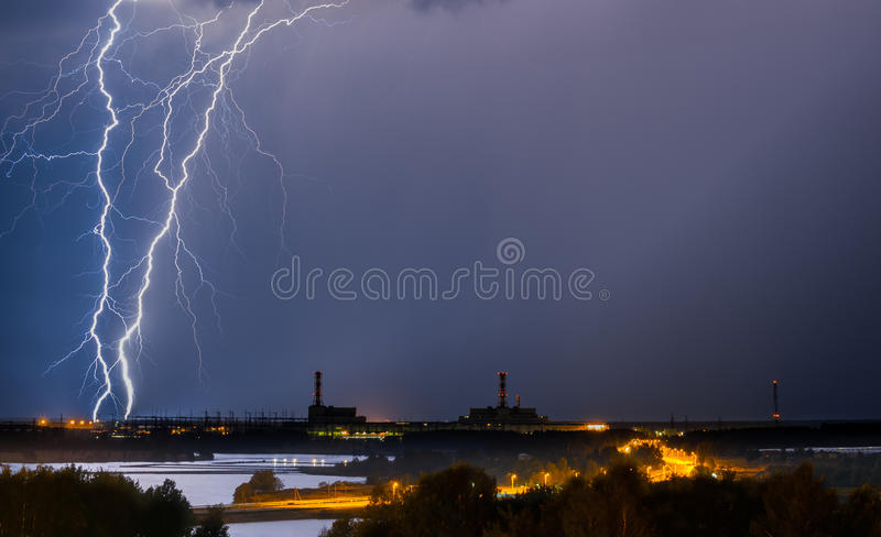 Thunderstorm above power plant. With gorgeous lightning at night stock photo