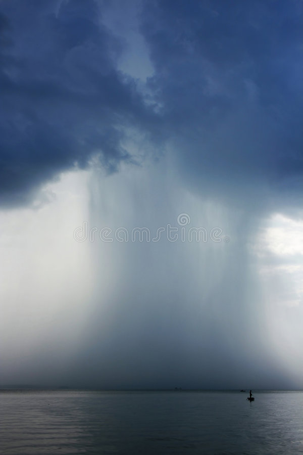 Thunderstorm cloudburst. The effective sky and lake stock photography