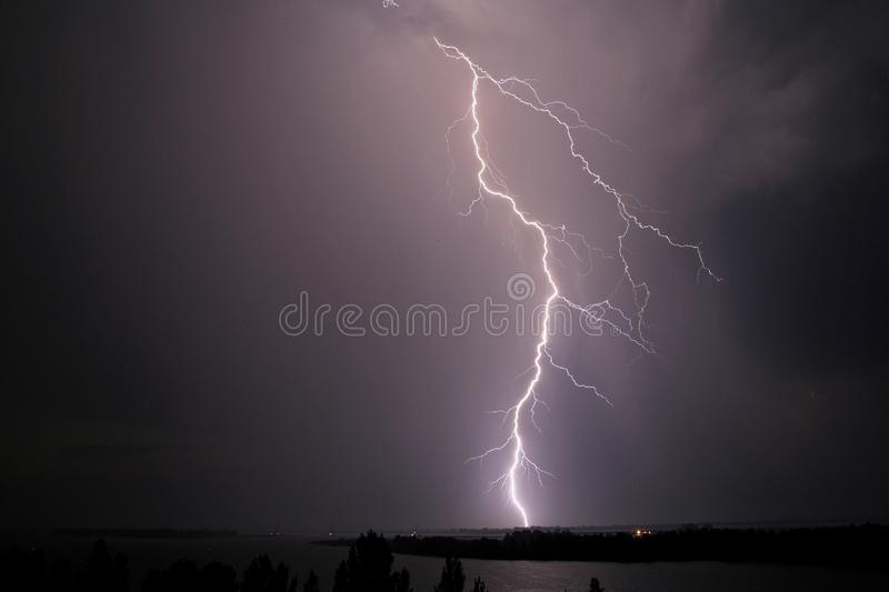 Thunderstorm and lightning strike over the river at night stock photography