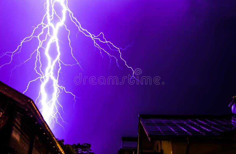 Thunderstorm in the night: Lightning on the sky, neighbourhood, Austria. Powerful Lightning on the cloudy sky, building in foreground, Austria thunderstorm stock photo