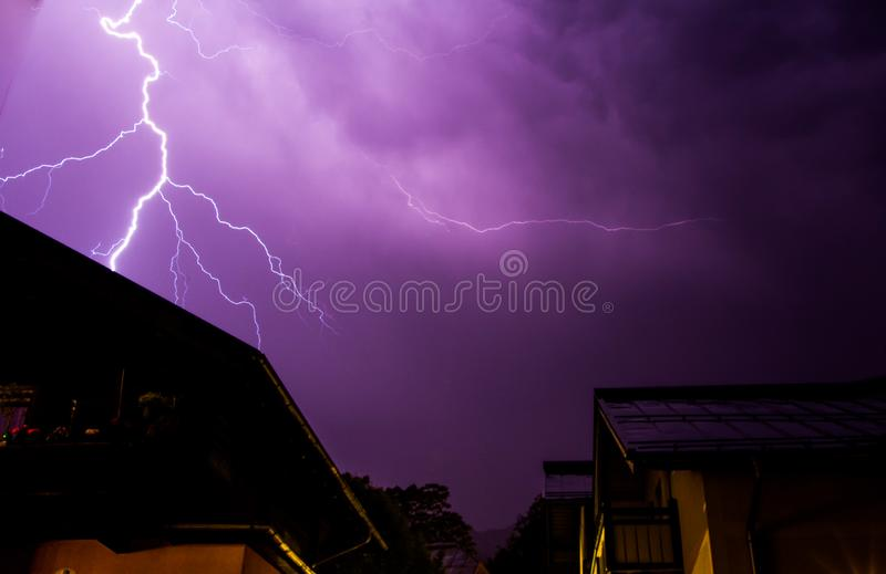 Thunderstorm in the night: Lightning on the sky, neighbourhood, Austria. Powerful Lightning on the cloudy sky, building in foreground, Austria thunderstorm royalty free stock photos
