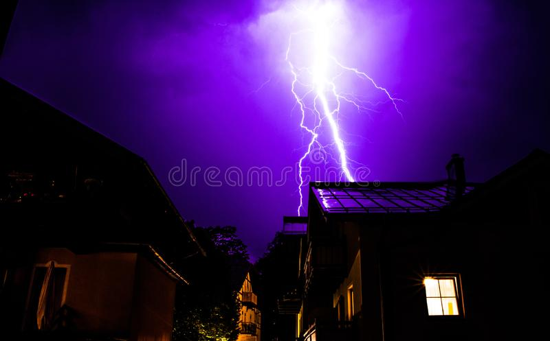 Thunderstorm in the night: Lightning on the sky, neighbourhood, Austria. Powerful Lightning on the cloudy sky, building in foreground, Austria thunderstorm stock images