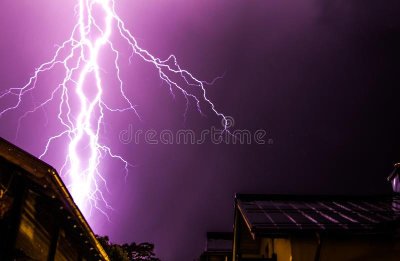 Thunderstorm in the night: Lightning on the sky, neighbourhood, Austria. Powerful Lightning on the cloudy sky, building in foreground, Austria thunderstorm royalty free stock image