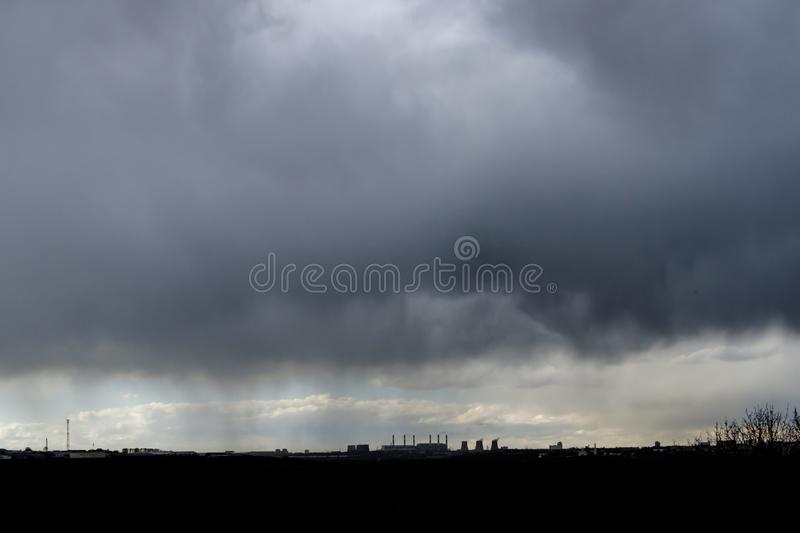 Thunderstorm over the city on a summer evening. Monstrous clouds over industrial buildings. Apocalyptic landscape. Thunderstorm over the city on a summer evening royalty free stock images