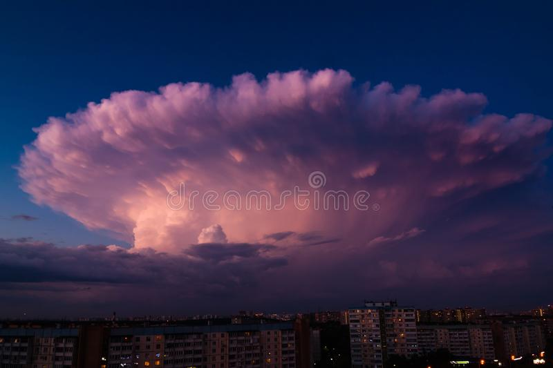 Thunderstorm in shape of explosion over the city on a warm summer evening. Cumulonimbus Incus cloud in a shape of nuclear mushroom. Thunderstorm in shape of royalty free stock photos