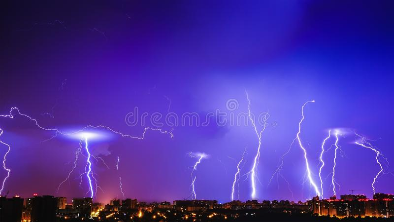 Thunderstorms vivid blue sky and many lightnings above night city stock image