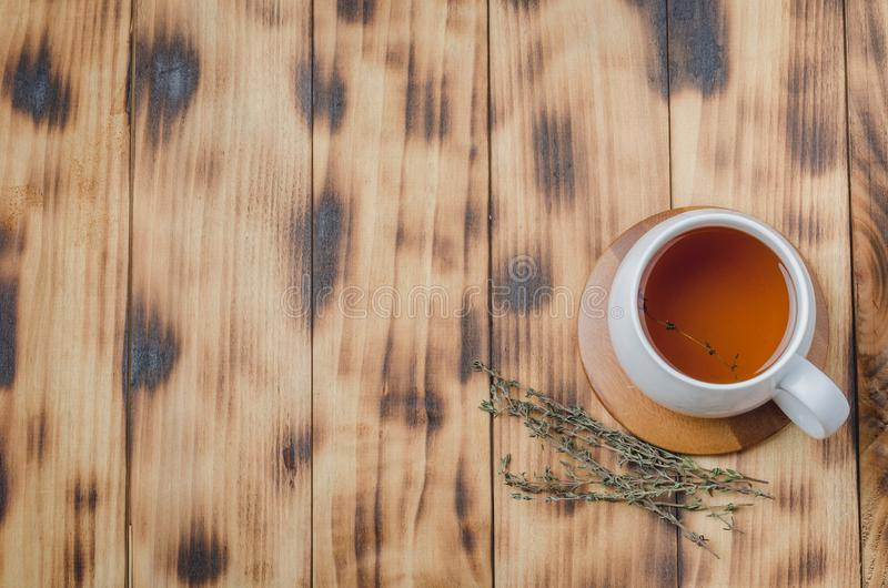 Thyme herbal tea in a white cup on a wooden table. View from above, space for a text. Top, health, aromatic, mug, beverage, background, green, hot, drink royalty free stock photo