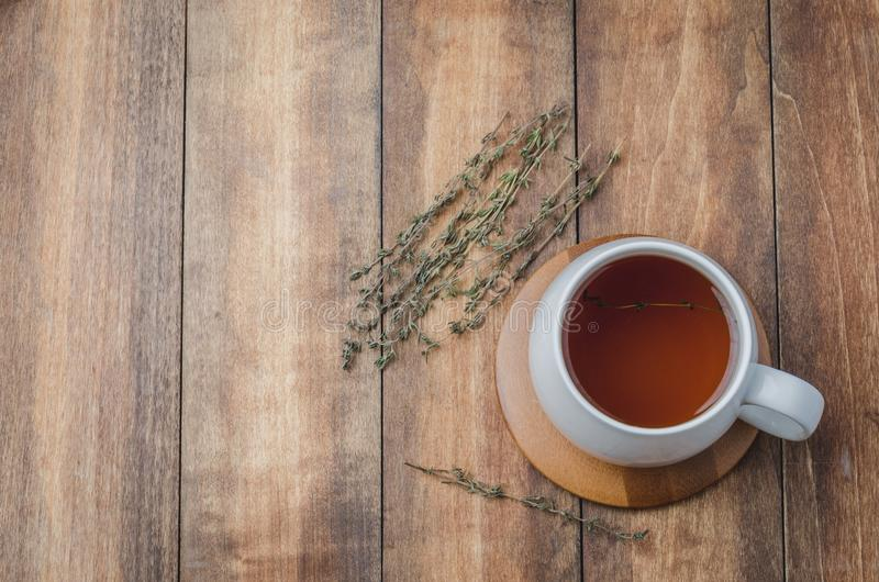 Thyme herbal tea in a white cup on a wooden table. View from above, space for a text. Top, health, aromatic, mug, beverage, background, green, hot, drink royalty free stock images