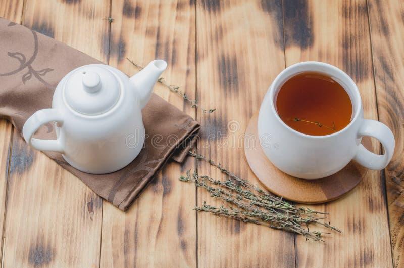 Thymian-Kräutertee, Blick aus Hochwinkel auf eine weiße Tasse mit Tee und Wasserkocher auf einem Holztisch lizenzfreie stockbilder