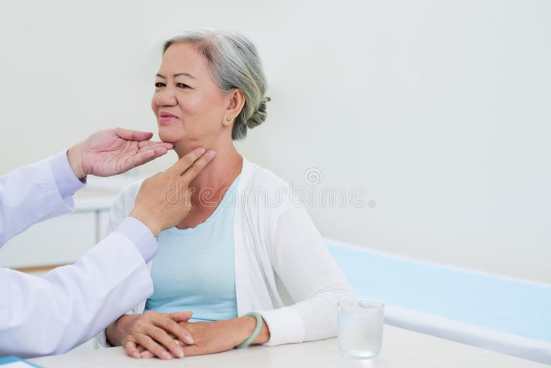 Thyroid check-up. Doctor checking thyroid gland of elderly Vietnamese woman stock photo