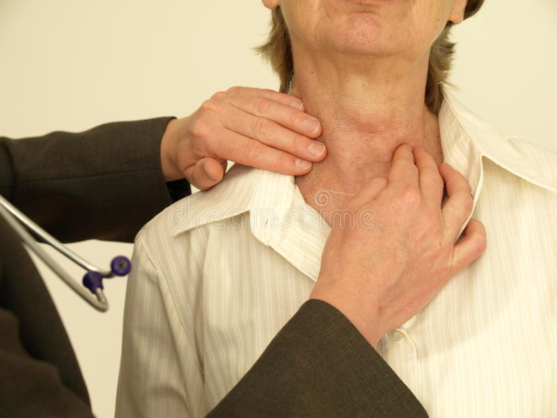Thyroid gland. Doctor checking senior woman's thyroid gland, close up stock photography