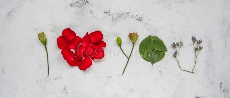 Ti amo - fatto dei fiori, dei petali e delle foglie fotografie stock