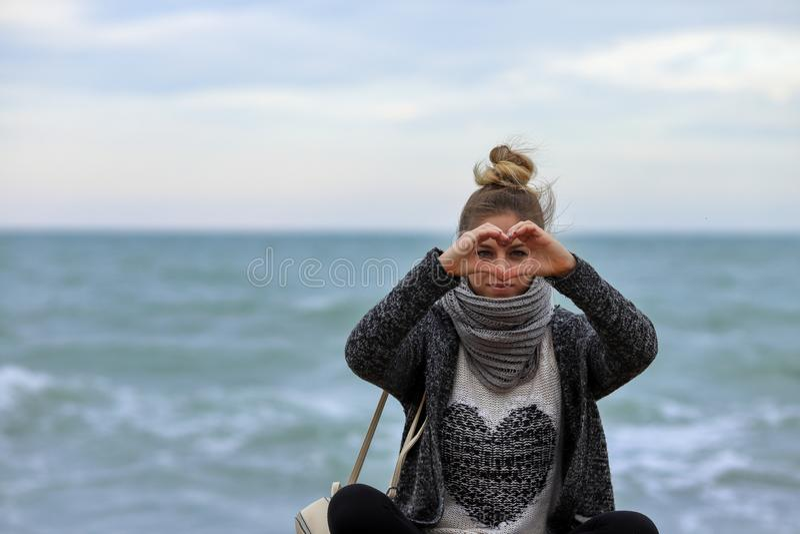 Ti amo Inviigli il mio cuore La bella ragazza mostra a mani il segno del cuore Giovane seduta bionda sulle pietre con il mare sop fotografia stock libera da diritti
