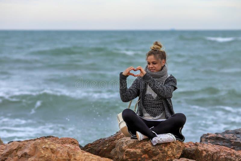 Ti amo Inviigli il mio cuore La bella ragazza mostra a mani il segno del cuore Giovane seduta bionda sulle pietre con il mare sop immagini stock libere da diritti