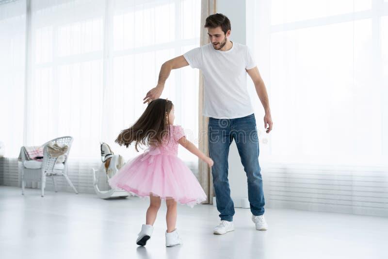 Ti amo, papà! Il giovane bello sta ballando a casa con la sua bambina Giorno felice del ` s del padre! fotografia stock