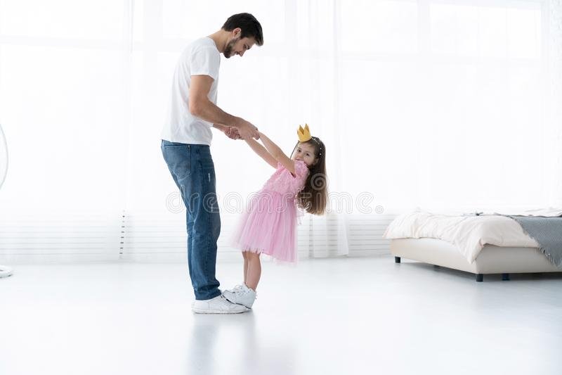 Ti amo, papà! Il giovane bello sta ballando a casa con la sua bambina Giorno felice del ` s del padre! immagine stock libera da diritti