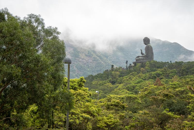 Tian dębnik wielki Buddha na górze z zielonym lasowym przedpola i chmur nieba tłem obrazy stock
