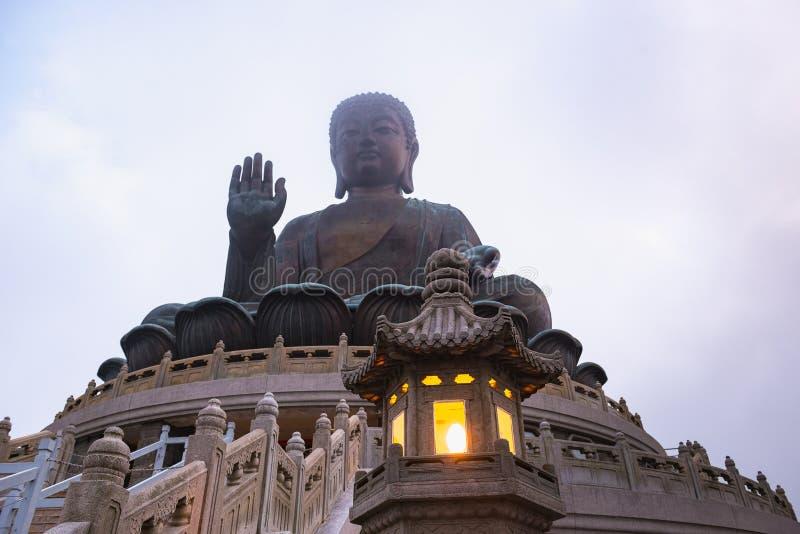 Tian Tan Buddha The Big Buddha statue in Lantau, Hong Kong, cloudy foggy evening, lit lantern in foreground. Tourism and stock photo