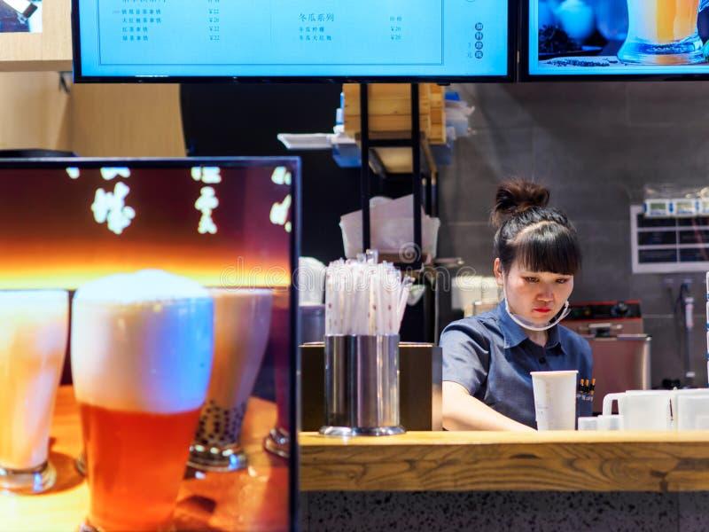 TIANJIN, CHINA - 7 DE OCTUBRE DE 2019 - El empleado asiático del puesto de té de burbuja chino prepara una bebida para los client imagen de archivo libre de regalías