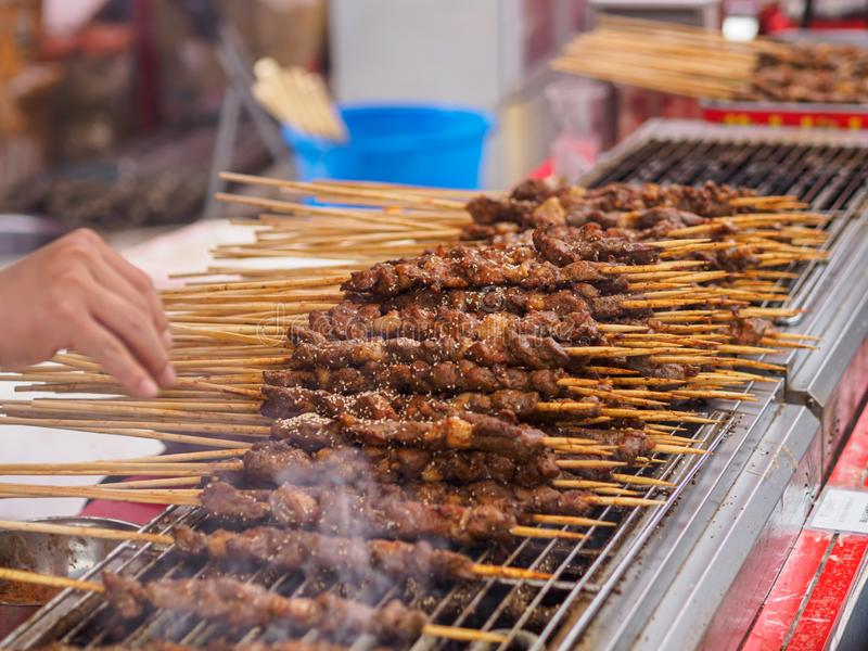 TIANJIN, CHINA - 6 OCT 2019 - Close up of grilled Xinjiang style lamb skewers cooking over a charcoal fire. TIANJIN, CHINA - 6 OCT 2019 - Close up of Xinjiang stock photo