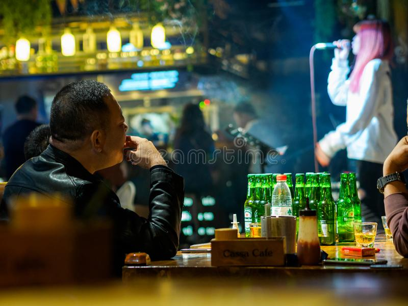 TIANJIN, CHINA - 5 OCT 2019 - Asian Chinese man drinks and smokes at a live music bar in Tianjin, China royalty free stock photo