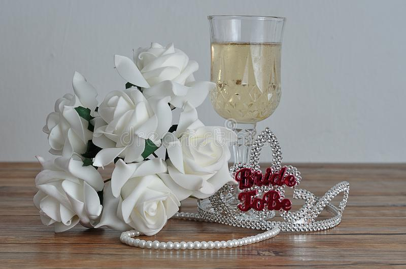 A tiara with the words bride to be displayed with a glass of champagne, white roses and a string of pearls royalty free stock images